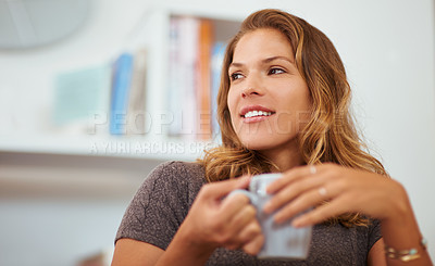 Buy stock photo Shot of a young woman enjoying a warm beverage at home