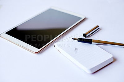 Buy stock photo High angle shot of a tablet and a notepad on a table