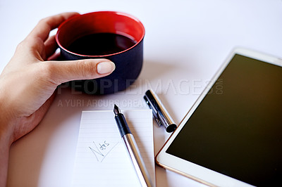 Buy stock photo High angle shot of a cup of coffee in a businesswoman's hand and a tablet and notepad on her desk