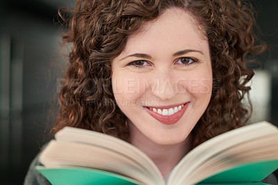 Buy stock photo Portrait of a young woman reading a book at home