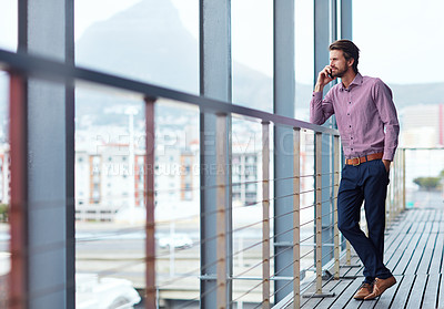 Buy stock photo Shot of a young businessman talking on a phone outside of an office building
