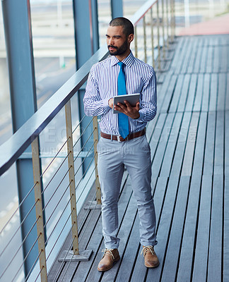 Buy stock photo Shot of a young businessman using a digital tablet outside of an office building