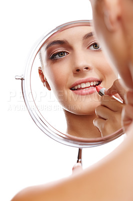 Buy stock photo Over the shoulder studio shot of a beautiful woman applying lipstick reflected in a mirror