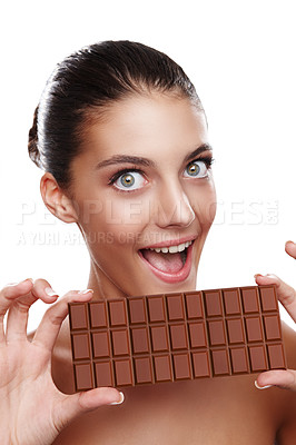Buy stock photo Studio portrait of an attractive young woman about to bite into a slab of chocolate