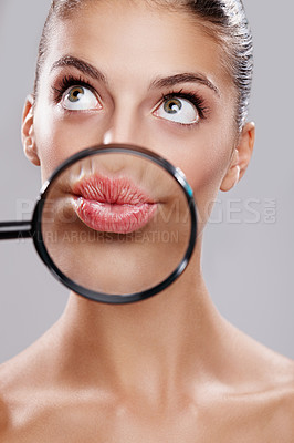 Buy stock photo Studio shot of a beautiful woman with a magnifying glass in front of her mouth