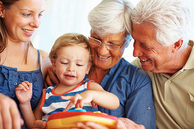 Buy stock photo Young boy playing a toy with his family