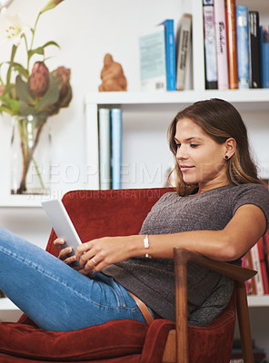 Buy stock photo Shot of a young woman relaxing with a digital tablet at home