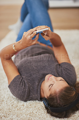 Buy stock photo Shot of a young woman relaxing at home and listening to music on her phone