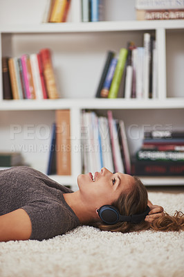 Buy stock photo Shot of a young woman relaxing at home and listening to music