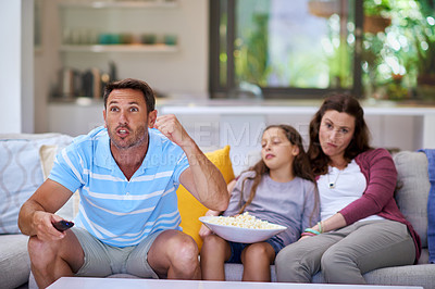 Buy stock photo Cropped shot of a man watching sports on the TV while is family sits bored in the background