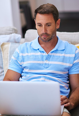 Buy stock photo Cropped shot of a mature man using his laptop while sitting on the sofa