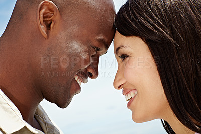Buy stock photo Shot of an affectionate couple standing face to face outside