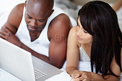 Buy stock photo Shot of a young couple lying in bed together using a laptop