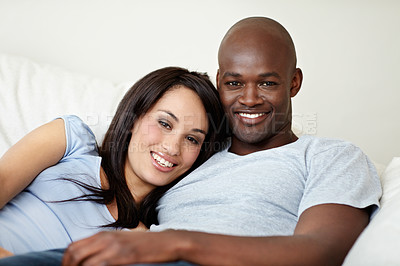 Buy stock photo Portrait of an affectionate young couple lying in bed together