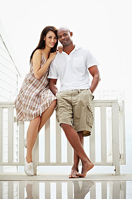Buy stock photo Portrait of a young couple leaning on the railing of their balcony