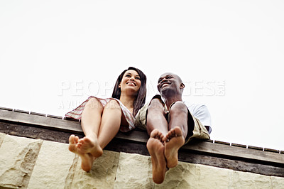 Buy stock photo Low angle shot of a young couple sitting together on the edge of a boardwalk