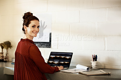 Buy stock photo Portrait of a woman looking over her shoulder while working on a laptop