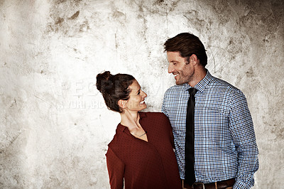 Buy stock photo Shot of an affectionate couple looking at each other while standing against a wall