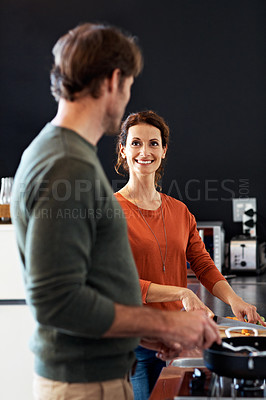 Buy stock photo Shot of a happy couple cooking together in their kitchen