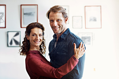 Buy stock photo Portrait of an affectionate couple standing arm in arm in their living room