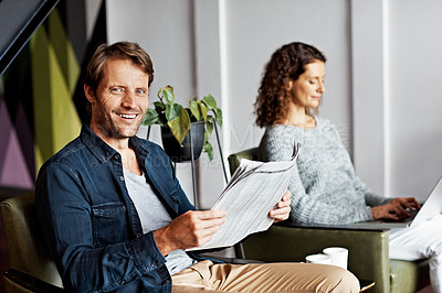 Buy stock photo Portrait of a mature couple sitting in their living room reading the newspaper and using a laptop