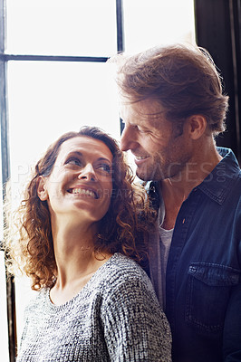Buy stock photo Shot of an affectionate couple standing by a window