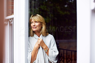 Buy stock photo Shot of a mature woman clutching her sweater while looking out of her living room window