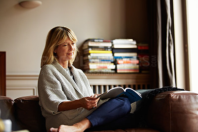 Buy stock photo Shot of a mature woman reading a book while sitting on her sofa