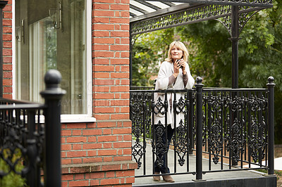 Buy stock photo Shot of a mature woman leaning against the railing of her front porch