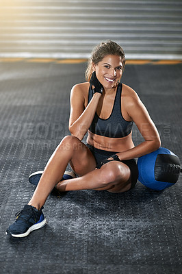 Buy stock photo Full length portrait of a young woman sitting beside a kettle bell after her workout