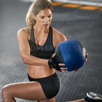 Buy stock photo Cropped shot of a young woman working out with a medicine ball at the gym