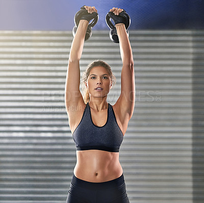 Buy stock photo Cropped portrait of a young woman working out with kettle bells at the gym