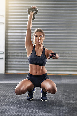 Buy stock photo Full length shot of a young woman working out with a kettle bell at the gym