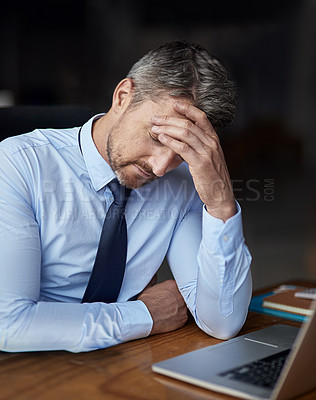 Buy stock photo Cropped shot of a mature businessman looking anxious while working in his office