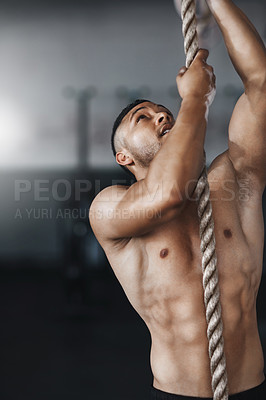 Buy stock photo Cropped shot of a young man climbing a rope at the gym