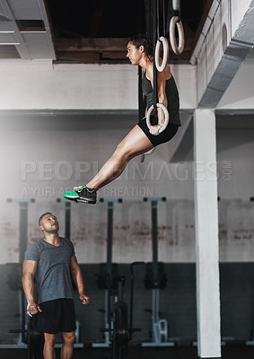 Buy stock photo Full length shot of a young woman working out on the gymnastics rings while her trainer looks on