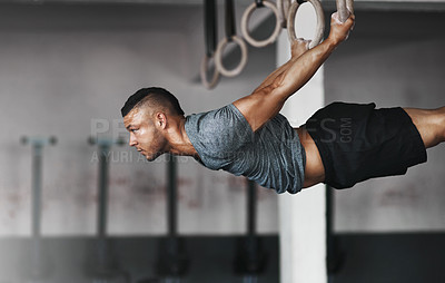 Buy stock photo Cropped shot of a young man working out on the gymnastics rings