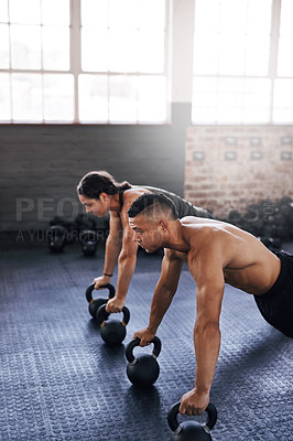 Buy stock photo Cropped shot of two young athletes working out in the gym