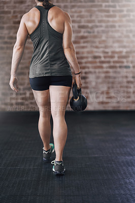 Buy stock photo Rearview shot of a young woman working out in the gym