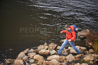 Buy stock photo Shot of a hiker climbing over rocks by the
