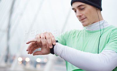 Buy stock photo Shot of a young man checking is watch while out for a run on a wet morning
