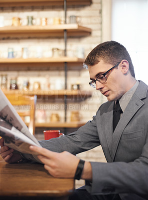 Buy stock photo Cropped shot of a young businessman reading the morning paper