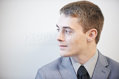 Buy stock photo Studio shot of a young businessman standing against a grey background