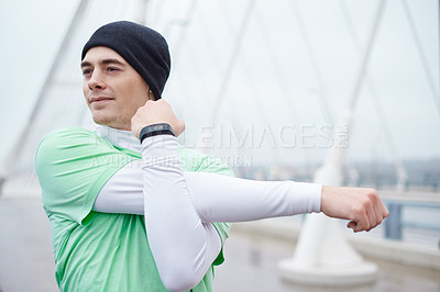 Buy stock photo Shot of a man stretching before his run