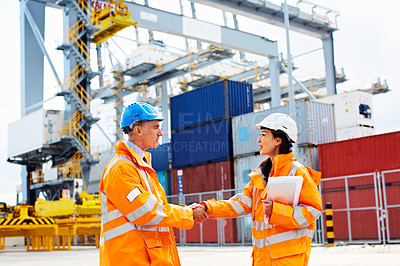 Buy stock photo Portrait of two workers shaking hands on a commercial dock
