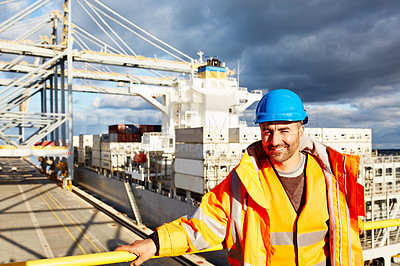 Buy stock photo Portrait of a man in workwear standing on an overhead walkway at a large commercial dock