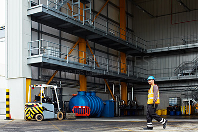 Buy stock photo Shot of a dock worker walking in front of a large warehouse on a commercial dock