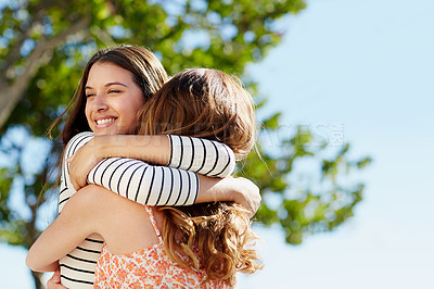Buy stock photo Shot of two young friends hugging while enjoying a day outside together