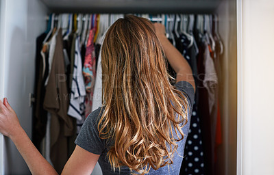 Buy stock photo Rearview shot of a young woman standing in front of her closet choosing something to wear