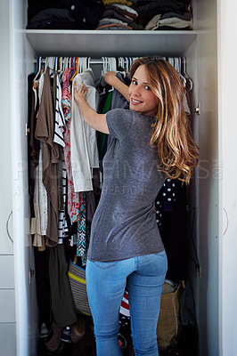 Buy stock photo Portrait of a young woman standing in front of her closet choosing something to wear